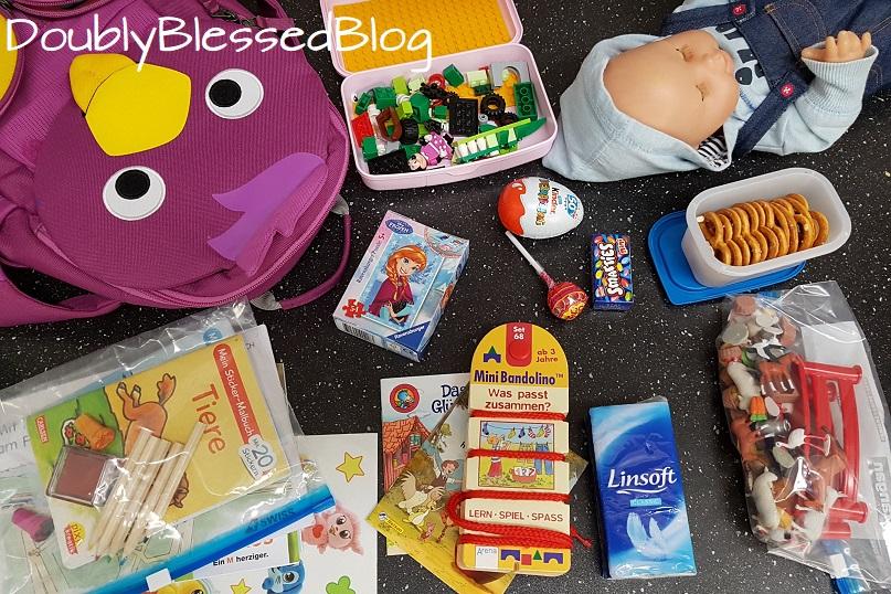 Inhalt des Kinderrucksacks zur Beschäftigung während dem Flug für ein Mädchen. Minipuzzle, Puppe, Lego Classic Box mit Legotape, Bandolino, Tiersammlung, Stempel, Malbüchlein, Farbstifte, Sticker, Pixibücher, Smarties, Überraschungsei, Lollipop